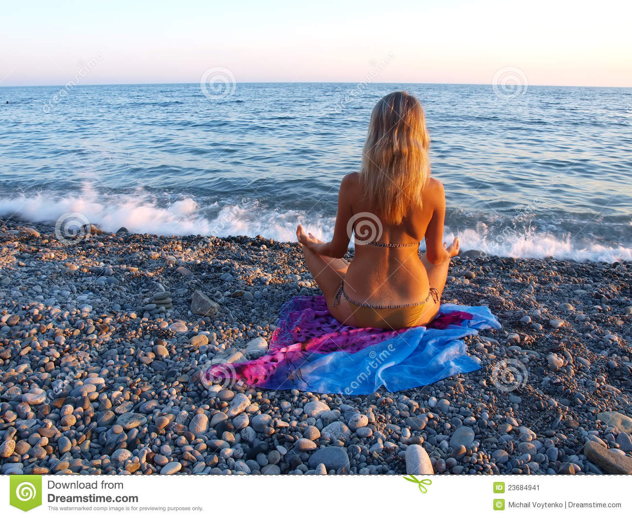 Young Woman Sitting On A Stony Beach Stock Image.