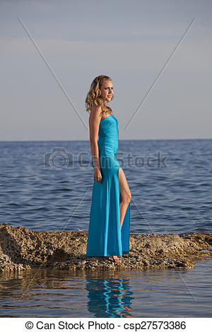 Pictures of Woman in long dress on stony beach.