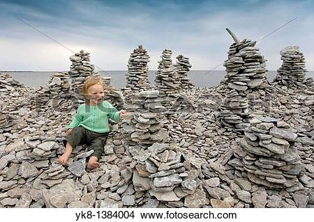 Stock Photo of Two Years Old Kid Girl Buidling Stone Tower on.