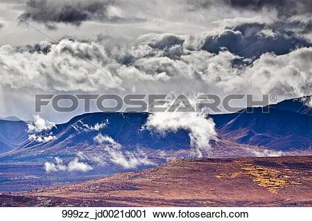 Stock Photography of Storm clouds gather over a ridgeline in.