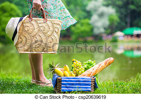 Stock Photography of Picnic basket with fruits, bread and hat on.