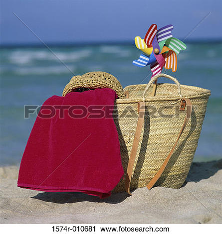 Stock Photography of Straw bag with a towel a hat and a pinwheel.