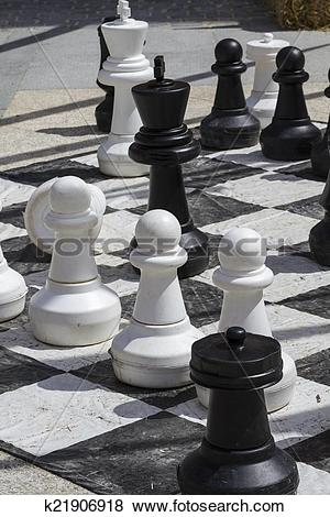 Pictures of Giant chess games in the street with large pieces.
