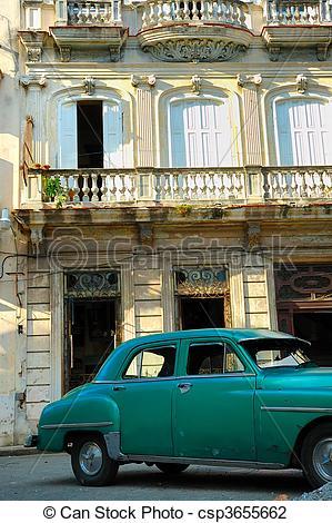 Stock Photo of Green vintage car parked in Havana street.