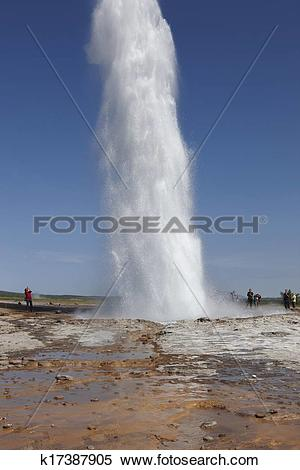Stock Image of Geyser Strokkur against blue summer sky, erupting.