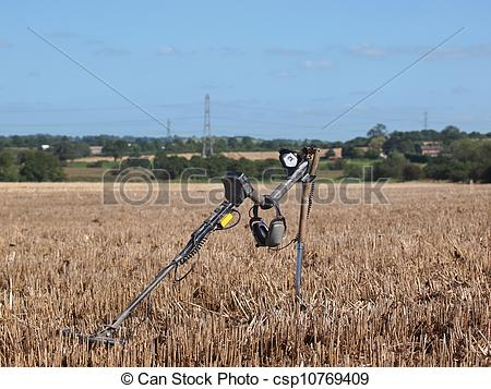 Stock Photography of metal detector in stubble field.