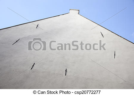 Picture of facade of old house with white stucco without windows.