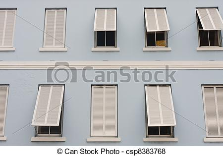 Pictures of White Shutters on Blue Stucco Building.