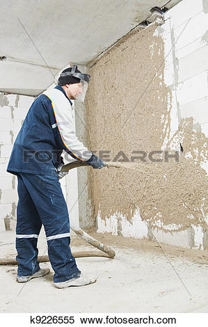 Stock Image of Plasterer at stucco work with liquid plaster.