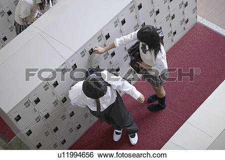 Stock Images of High school student at locker changing shoes.