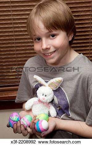 Stock Photo of Boy age 11 holding his newly dyed Easter eggs and.