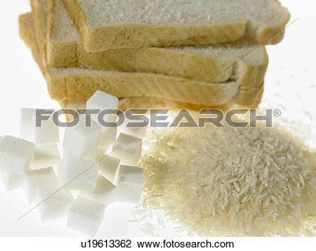 Stock Photo of White bread slices beside piles of sugar and rice.