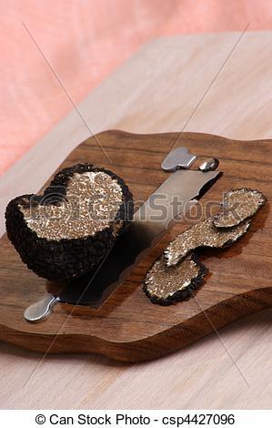 Stock Image of organic summer truffle on a truffle slicer.