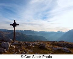 Picture of Girl prays in front of the mountain to the summit cross.