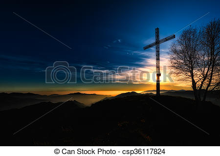 Stock Photo of Summit cross a mountain at sunset religious.