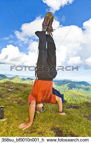 Stock Photo of Male hiker doing headstand on summit of Pyramid.
