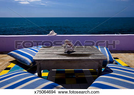 Stock Photo of inviting setting of table and cushions on the sun.