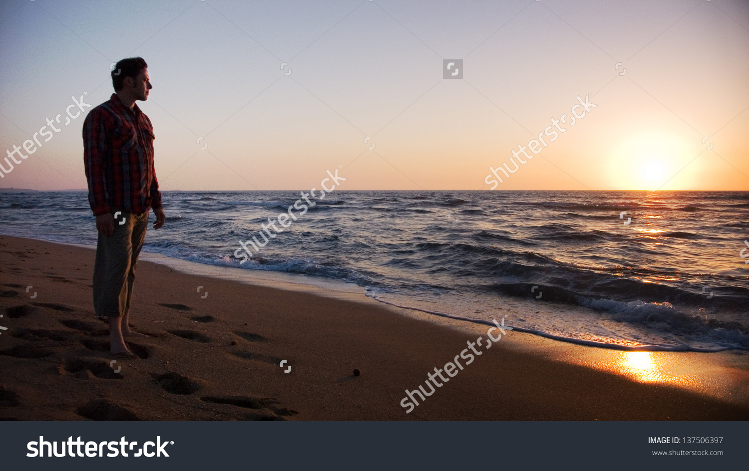 Man Standing On Beach Looking Into Stock Photo 137506397.