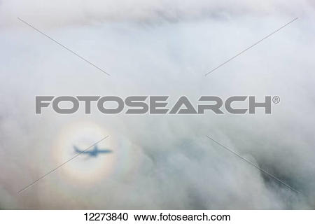 Stock Photography of The shadow of an airplane cast by a sundog on.