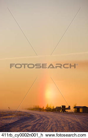 Stock Photo of A Sundog appears above the small planes parked on.