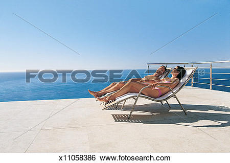 Stock Images of Couple Talk While Lying on Sun Loungers.