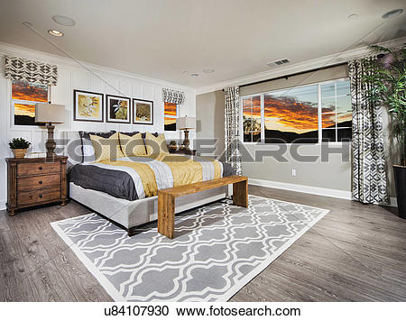 Stock Photography of Spacious bedroom with view of sunset through.