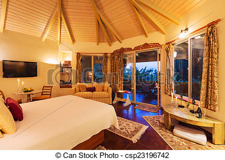 Stock Photo of Cozy Bedroom with Hardwood Floors at Sunset.