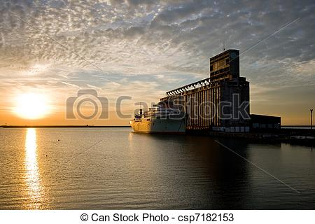 Stock Photos of Old ship and grain elevator at sunset.