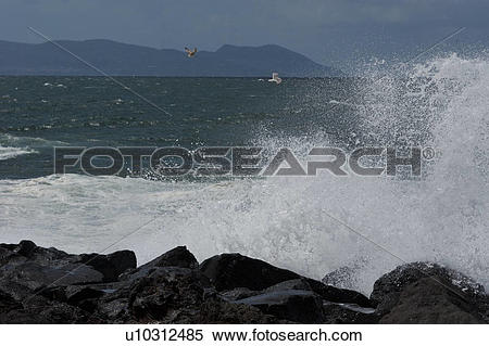 Stock Image of Sea surf breaking on rocks with blue sky, sea, and.