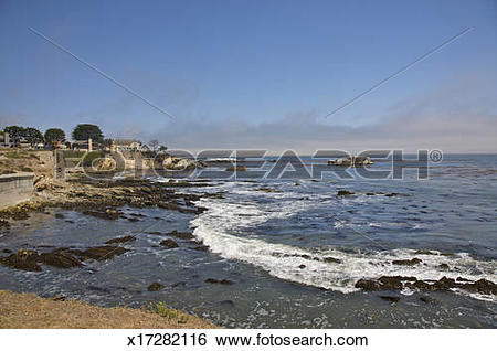 Stock Images of Late afternoon surf near rocks and cliffs.