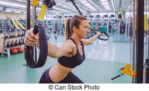 Stock Photo of Woman doing suspension training with fitness straps.