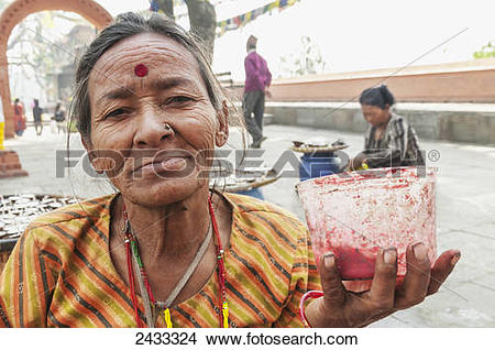 Stock Photo of A Hindu woman in Swayambhu temple painting thirth.