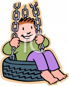 A Young Boy Riding In A Tire Swing.