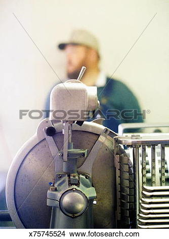 Stock Photo of Meat saw with on and off switch, man in background.