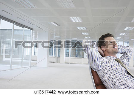 Stock Photo of Office worker leaning back in swivel chair, hands.
