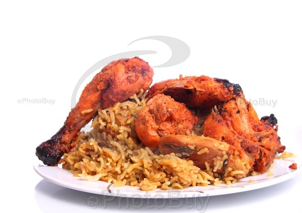 Pieces of tandoori chicken over chicken Biryani.