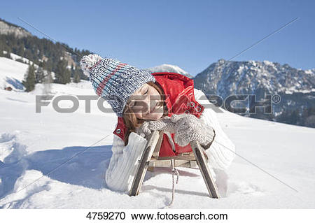 Stock Photography of Smiling woman lying on toboggan, Tannheimer.