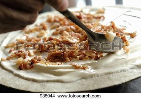 Stock Photo of Putting bacon on a tarte flambée 938044.