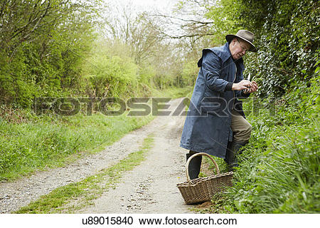 Stock Photography of A man in a long coat and boots foraging for.