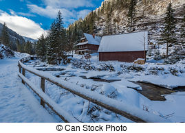 Stock Images of Frozen mountain river and wooden cottage in winter.