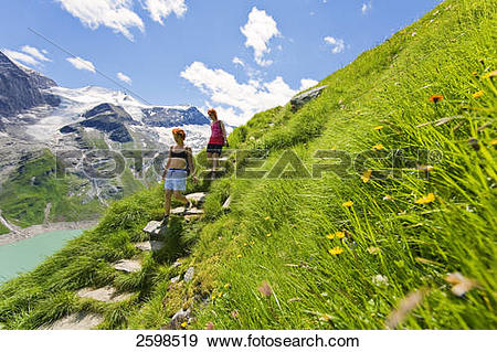 Stock Photograph of Hikers walking at lakeside, Hohe Tauern, Alps.