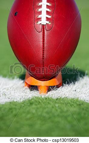 Stock Photography of American Football teed up for kickoff.