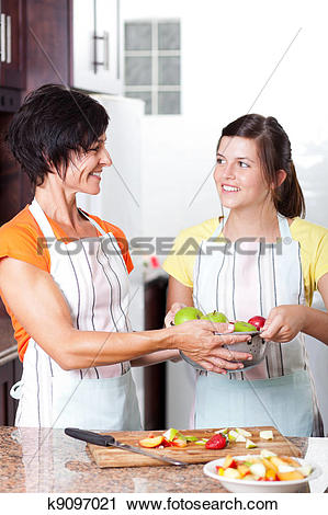 Stock Photography of teen girl helping mother in kitchen k9097021.