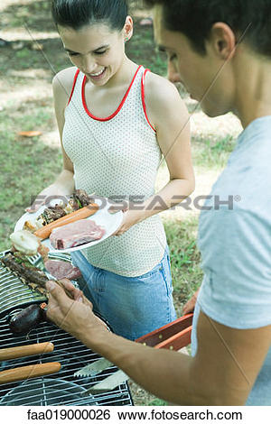 Stock Images of Man serving teen girl grilled meats from barbecue.