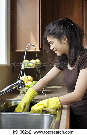 Stock Photo of Teen girl washing dishes at kitchen sink k9136252.