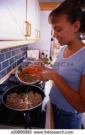 Stock Photo of Teen Girl Cooking Dinner x20895983.