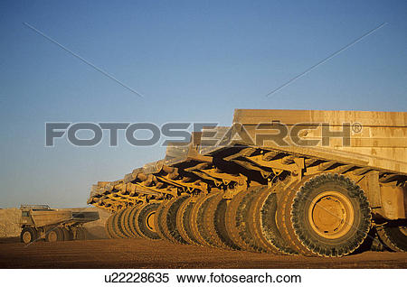 Stock Image of Ore hauling trucks in row Telfer Western Australia.