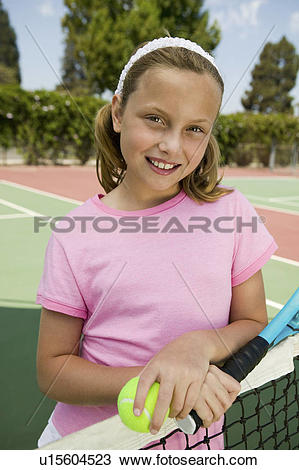Stock Photo of Young girl with tennis racket and ball by net at.