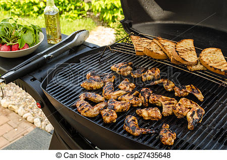 Stock Photo of Teriyaki chicken wings with garlic bread and herbs.
