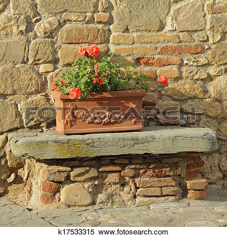 Stock Image of beautiful tuscan terracotta planter in front of old.